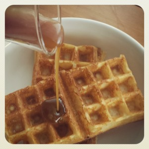 Picture of Elizabeth Marshall's American Yeast Raised Waffles with her Easy Bourbon Caramel Sauce pouring onto them